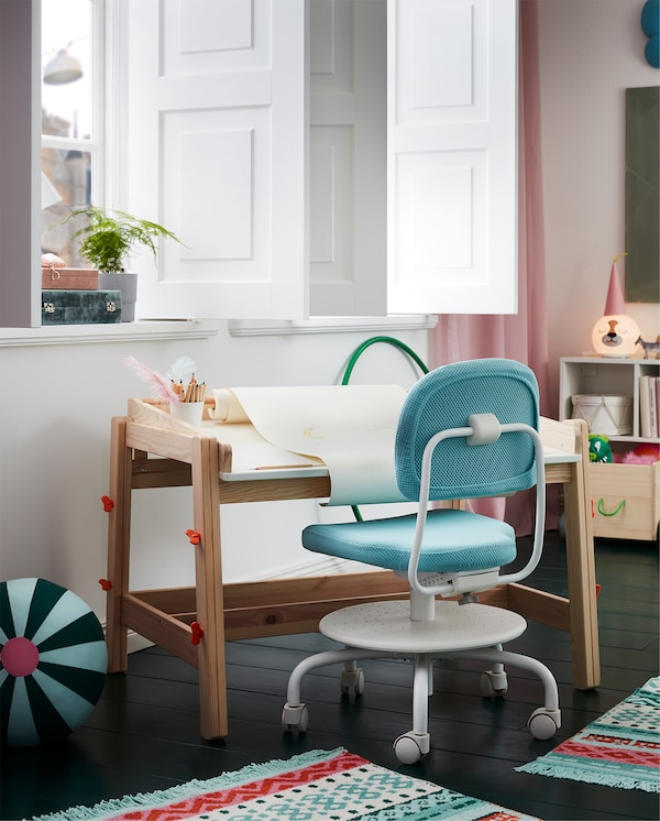 FLISAT children's desk with a drawing paper roll stands by a window, and a turquoise children's desk chair stands beside.