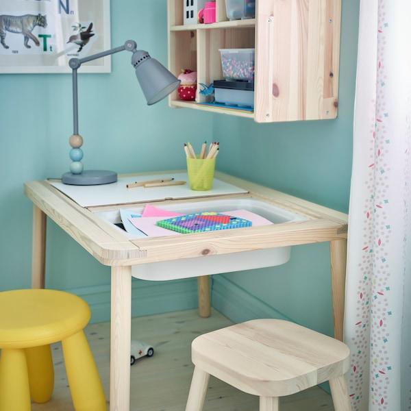 FLISAT pine table for children with white plastic bins underneath.