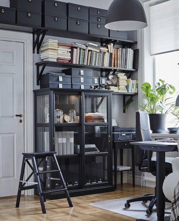 Floor to ceiling storage in a home office. A black step-stool makes it possible to reach the top of the shelving unit.