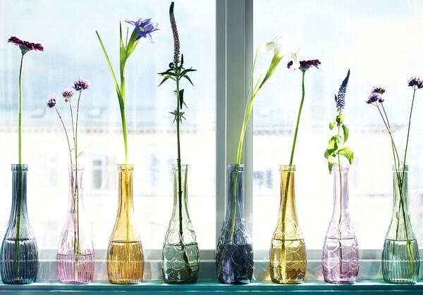 Floreros de varios colores alineados en el alféizar de una ventana con una sola flor dentro.