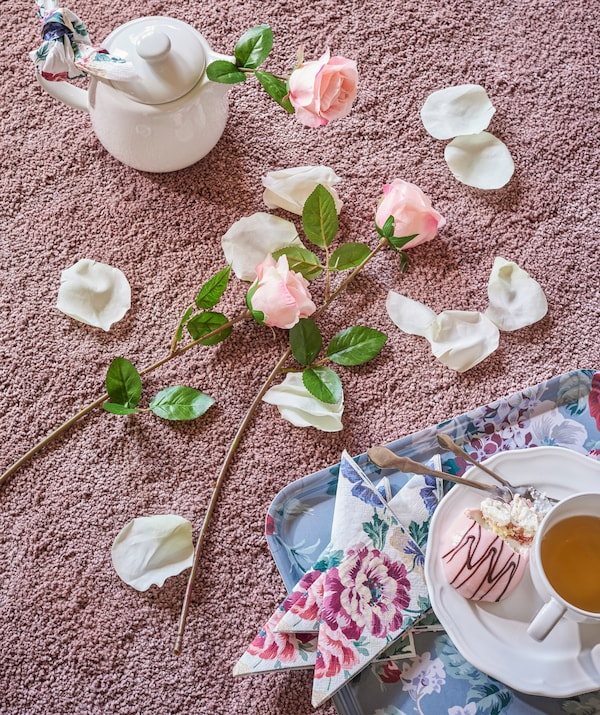 Flores y pétalos rosas y blancos sobre el suelo junto a una bandeja con una tetera sobre una alfombra rosa.