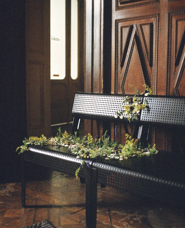 Flowers draped across two black metal chairs.