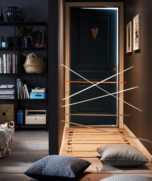 Flur, der vom Wohnzimmer wegführt, unterteilt durch eine FULLFÖLJA Kleberolle in Grau. Auf dem Boden sind u. a. DAGGRUTA Kissenbezüge zu sehen.