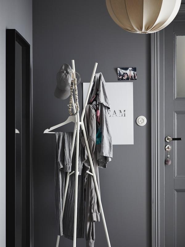 Flurbereich in einem grauen Farbschema. An der Eingangstür steht ein EKRAR Garderobenständer, an dem mehrere Kleidungsstücke hängen.