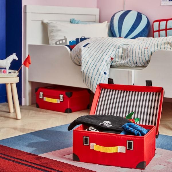 큰 배가 그려진 러그가 깔린 아이 방, 러그 위에 레드 색상의 FLYTTBAR 플뤼트바르 트렁크가 열려 있고 그 안에는 해적 옷이 들어 있는 모습
