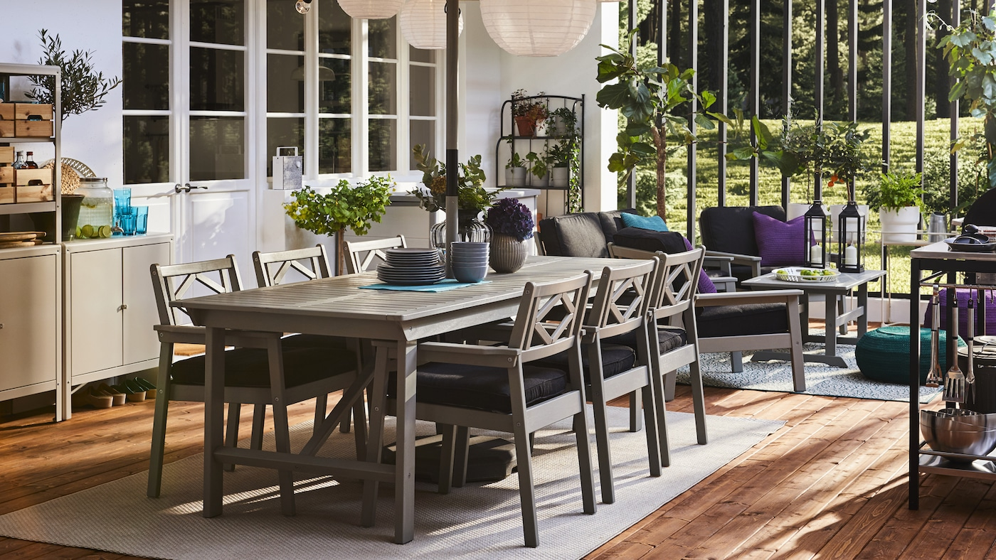 فناء به طاولة وكراسي بمساند للذراعين باللون الرمادي وتخزين ومصابيح معلقة مستديرة وأرضية خشبية.