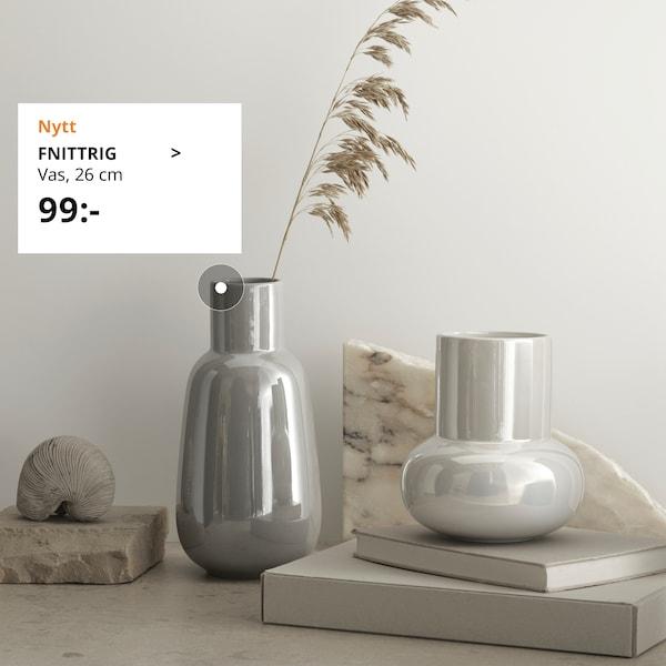 FNITTRIG vaser i två olika färger och storlekar står framför en vägg.