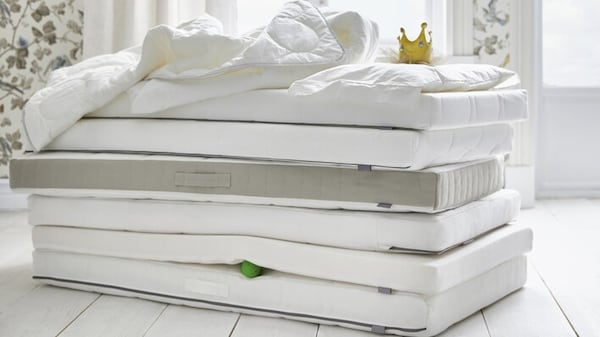 Foam and latex mattresses stacked on top of each other.