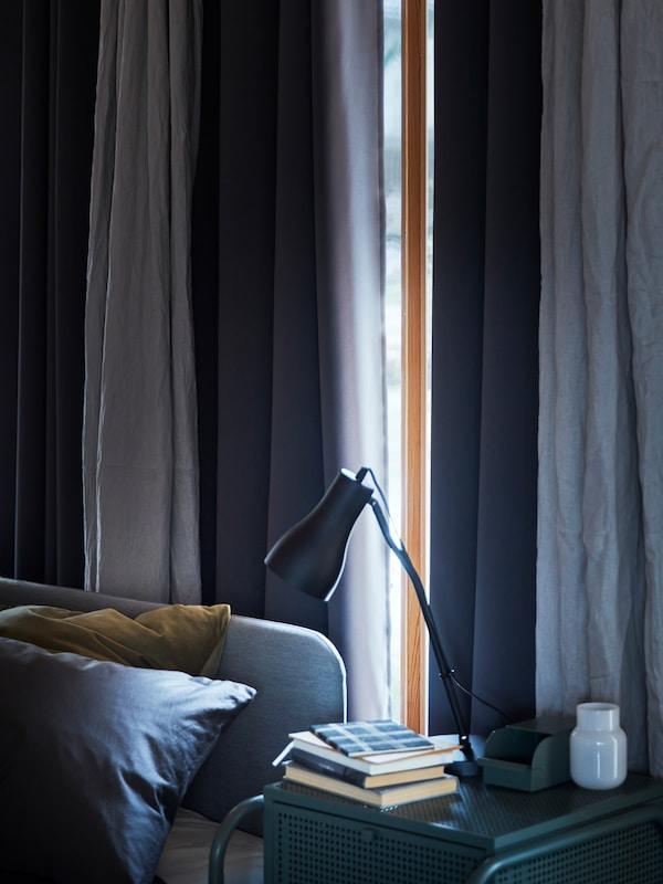 Fönster i ett sovrum med blå toner, där solen nästan helt döljs av HILLEBORG mörkläggningsgardiner.