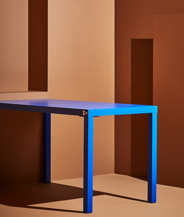 FÖRNYAD bright blue small table shown against a light brown background.