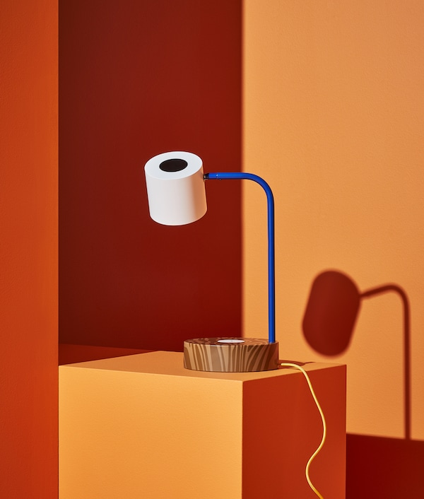 FÖRNYAD desk lamp that looks like the big eye of Darcel Disappoints against an orange background.