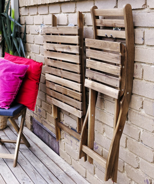Foldable wooden chairs hanging on a brick wall.
