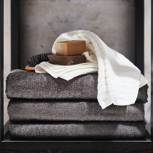 Folded VÅGSJÖN dark grey bath towels with bathroom accessories stacked on top