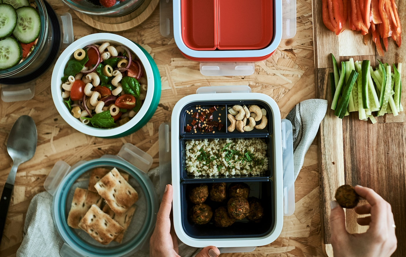 Food being packed into lunchboxes. One has compartments with different food, there's pasta salad in a round plastic tub.