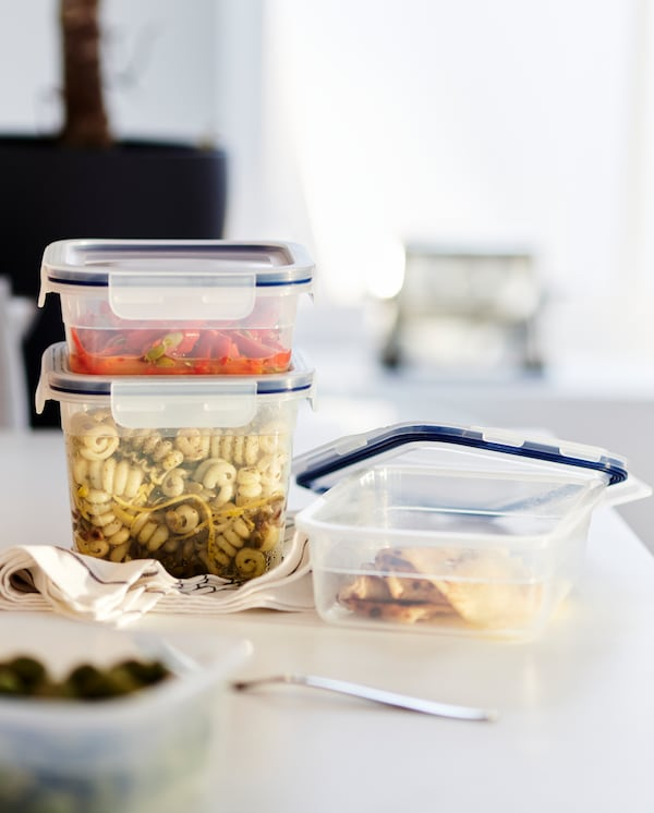 Food leftovers in three plastic food containers with lids, black/white tea towels and a fork on a white worktop.