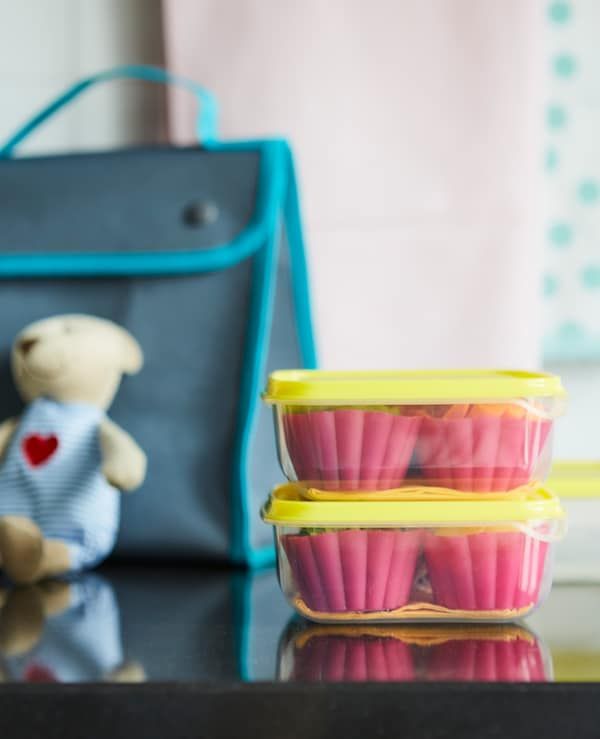 For a kid's lunch, stack 2 clear containers with  food divided by silicon muffin cups.