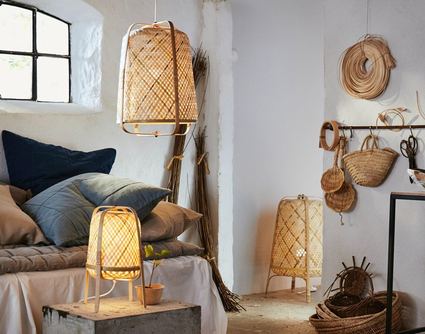 Forskellige lamper af bambus står i et stald-lignende rum.