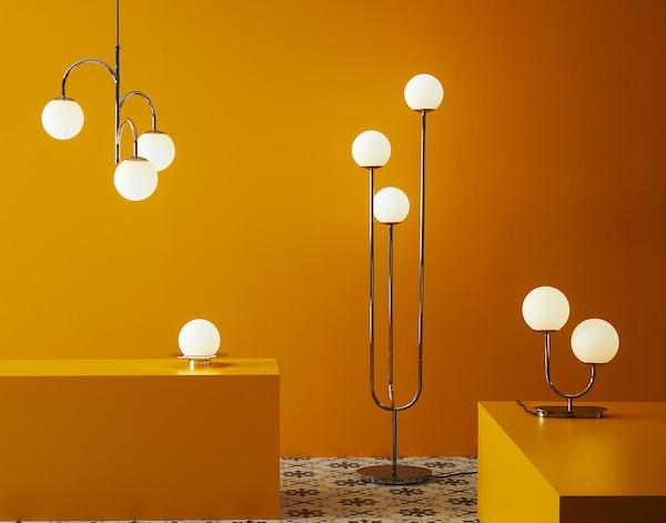 Forskellige lamper med runde glaskupler står og hænger i et gult rum.