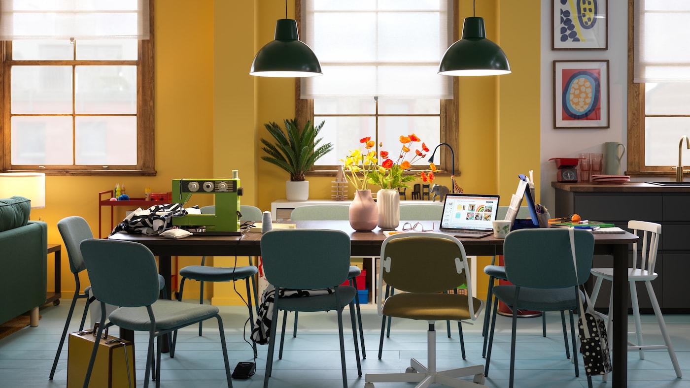 Forskjellige stoler rundt et mørkebrunt STRANDTORP uttrekkbart bord med ulike stasjoner til hverdagsaktiviteter.