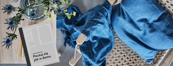fotel bambusowy z niebieską poduszką i kocem oraz książką leżącą na stole