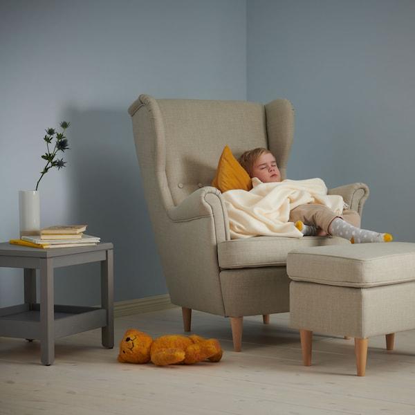 Fotelben alvó gyermek, mellette egy kisasztal, dekorációval, és egy maci a padlón.