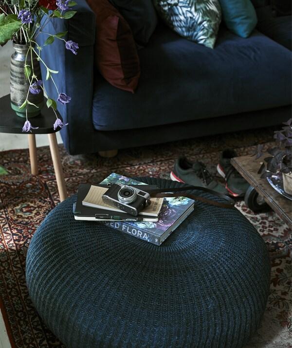 """Foto einer Kamera und einiger Bücher auf einem grossen Sitzhocker. Im Hintergrund ist STOCKHOLM 2017 3er-Sofa mit Bezug """"Sandbacka"""" in Dunkelblau zu sehen."""