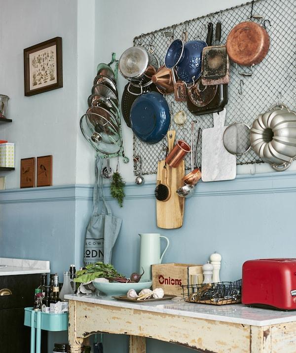 Foto einer Sammlung von Töpfen, Pfannen und Kochutensilien an einem Gitter in der Küche über einem rustikal wirkenden Ablagetisch, u. a. mit BEHÖVD Isolierkanne 1 L in Hellgrün/Beige.
