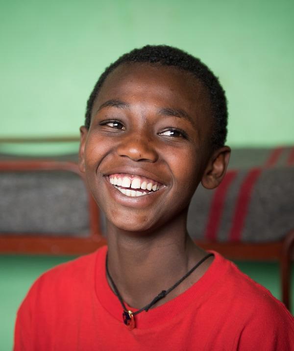 Fotografia de um rapaz sorridente com uma T-shirt vermelha