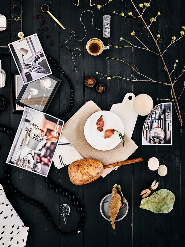 Fotografías, marcos, granos de café, una rama y un plato OFTAST con dos cebollas repartidos por una mesa de madera negra.