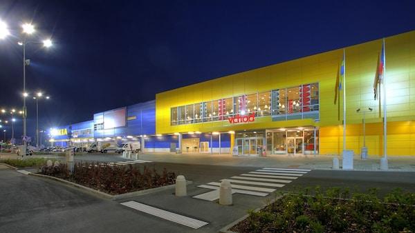 Fotografie obchodního domu IKEA za soumraku s parkovištěm v popředí.