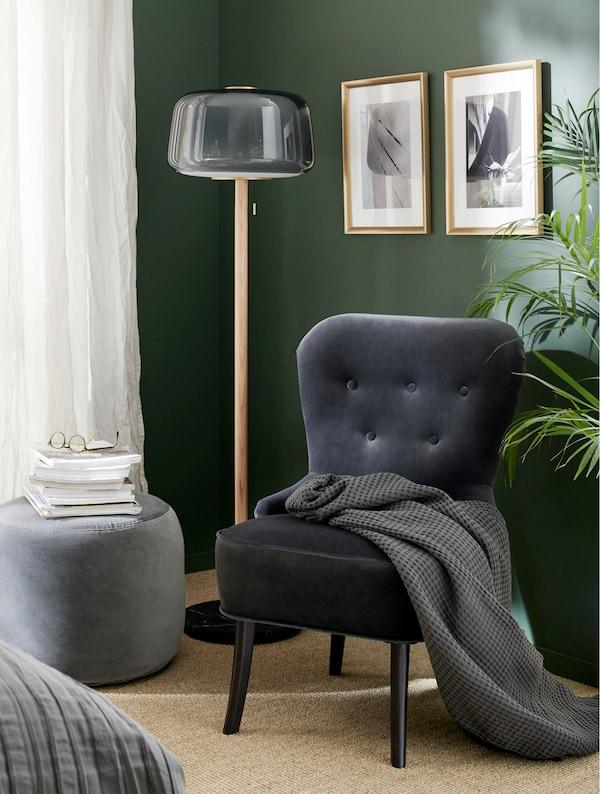 Fotoliu din catifea gri, un lampadar gri, un pouf gri închis, o păturică gri și rame aurii.