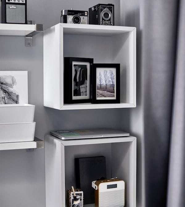 Fotos, Kameras und eine Stereoanlage finden sich in EKET Schrank in Weiß über dem Bett.