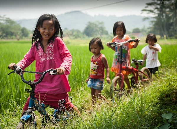 Four children playing and riding bikes in a field.