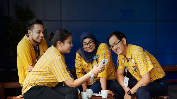 Four co-workers, two male and two female, are gathered around, sitting. A co-worker is holding up a white for while the other three are looking at her phone and smiling. There are three white mugs on a wooden table at the center of the group.