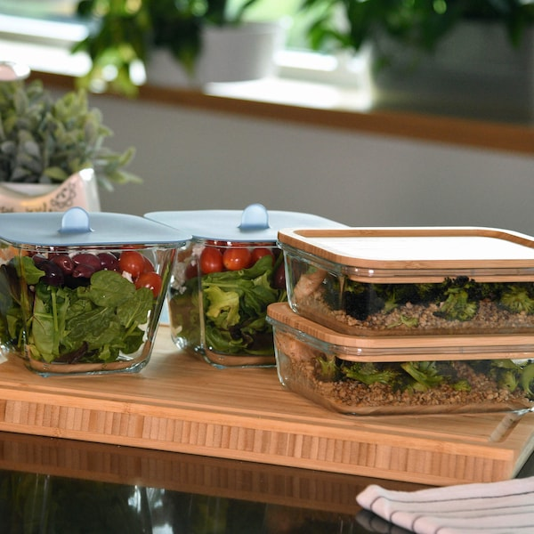 Four glass containers with lids with salad greenery and leftover meals inside.