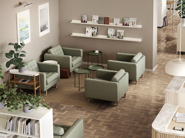 Four green LANDSKRONA armchairs with GLADOM tray tables between them. A MOSSLANDA picture ledge holds journals on the wall.