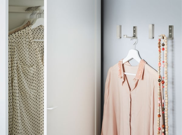 Four IKEA BJÄRNUM aluminium folding hooks on a wall next to a wardrobe, used to hang clothing and necklaces.