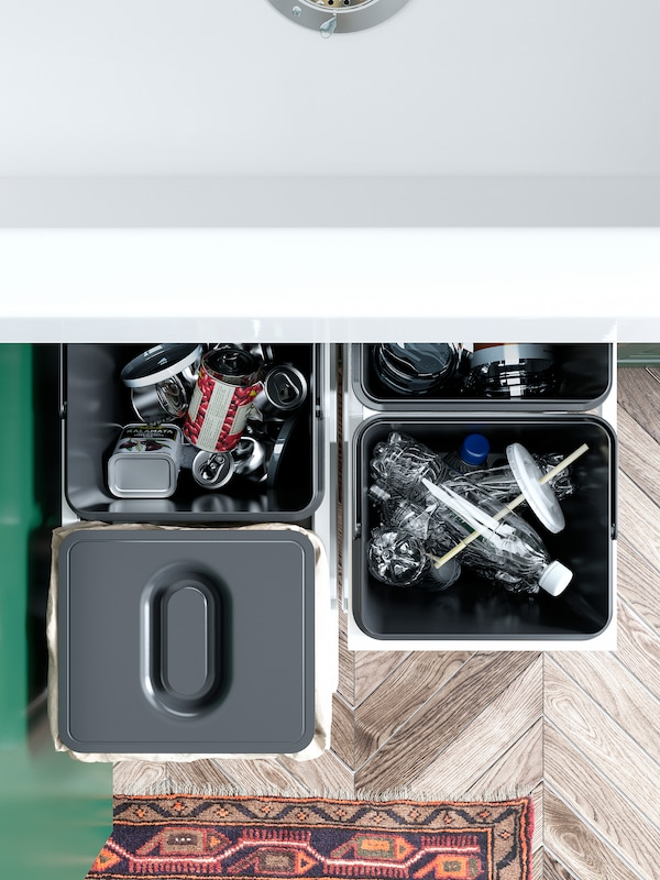 Four IKEA VARIERA black waste sorting bins filled with empty plastic bottles and cans. One bin has a lid on top.