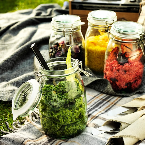Four KORKEN jars containing food on a picnic blanket