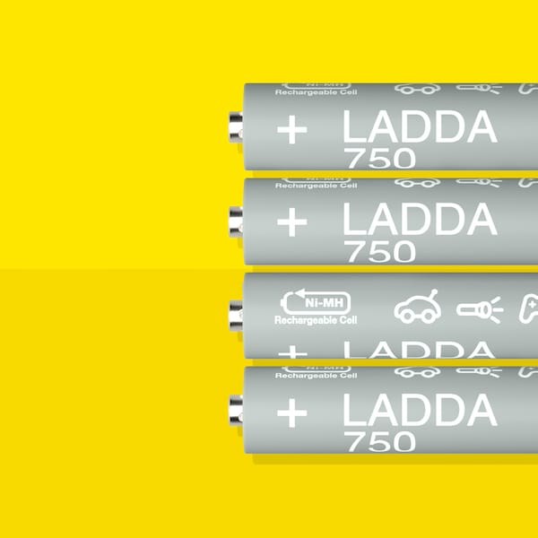 Four LADDA rechargeable batteries, HR03 AAA with a battery capacity of 750 mAh, lie in a row on a yellow surface.