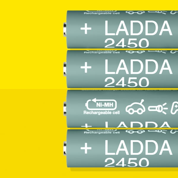 Four LADDA rechargeable batteries, HR6 AA with a battery capacity of 2450 mAh, lie in a row on a yellow surface.
