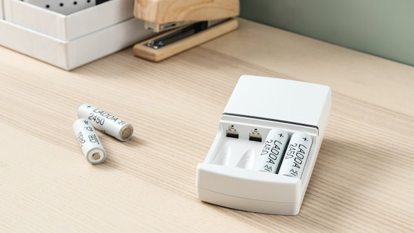 Four, LADDA rechargeable batteries in a white, KVARTS battery charger plugged in to a socket on a white wall.