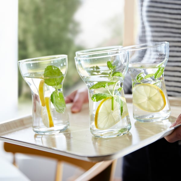 Four OMTÄNKSAM glasses on a leaning FÖRMEDLA tray. The anti-slip surface helps the glasses stand steady.