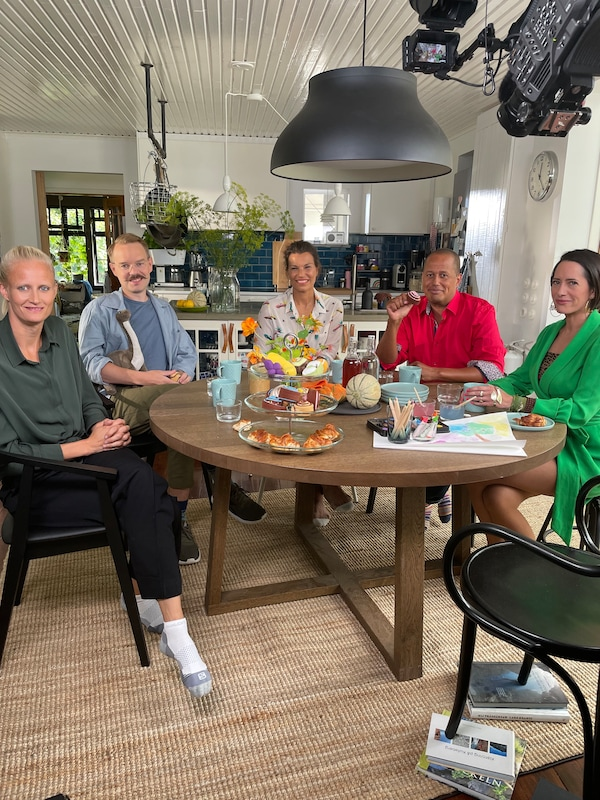 Four people at a dining table looking into the camera while being filmed.