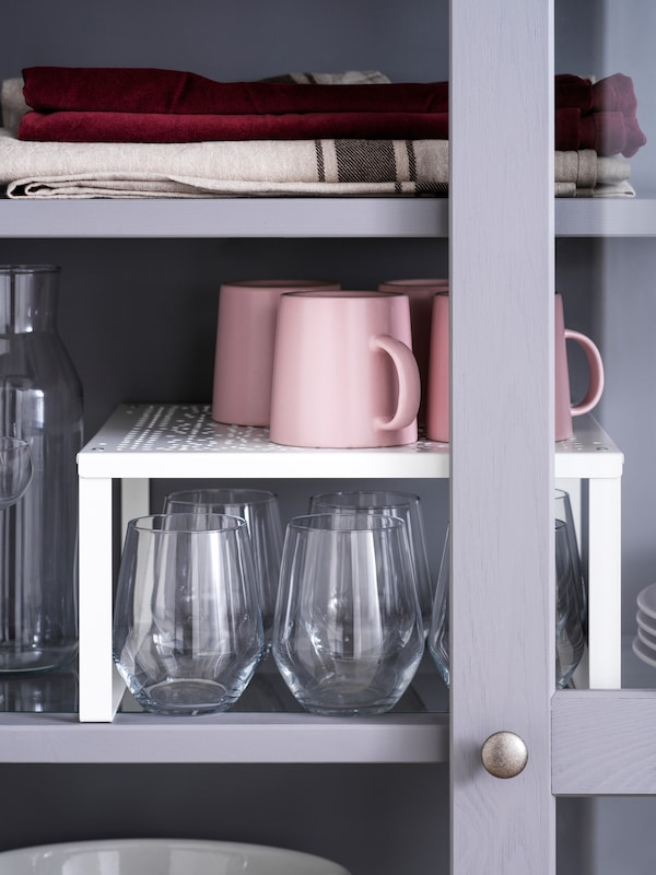 Four. pink mugs on a white VARIERA shelf insert that stands above several drinking glasses on a grey cabinet shelf.