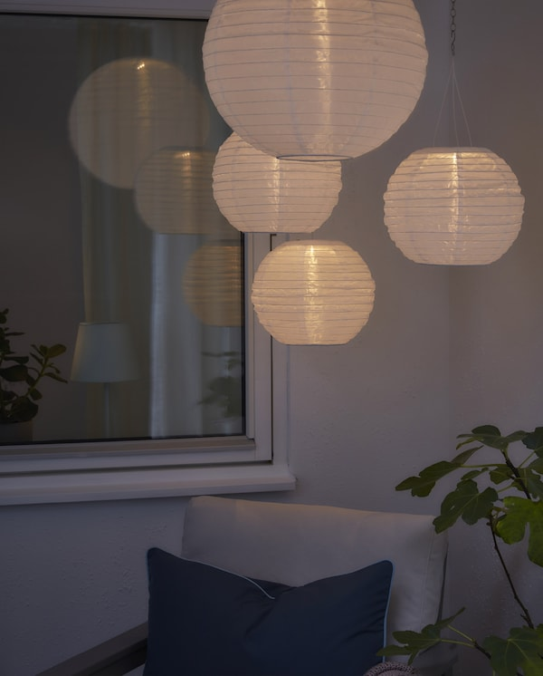 Four round, white solar-powered pendant lamps are creating a cosy mood lighting in a darkened outdoor space.