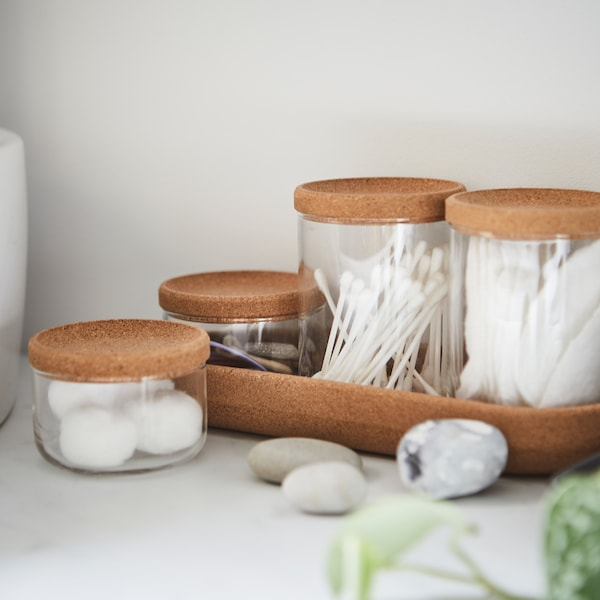 Four SAXBORGA glass jars in two different sizes with cork lids and a cork tray, holding cotton balls and Q-tips.