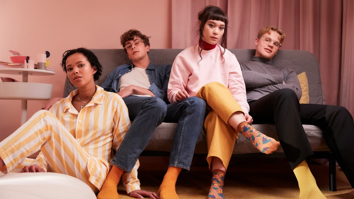 Four school friends sitting together in a sofa in a dorm room.