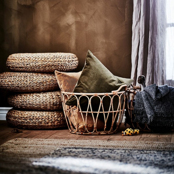 Four stacked stools made from banana fibre, two rattan baskets with pillows and a throw, a jute rug and a curtain.