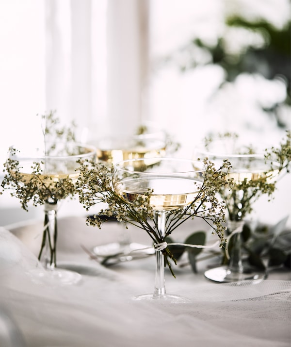 Four STORHET champagne coupes on a tray with tiny branches of small, wild flowers tied to the glass stems.
